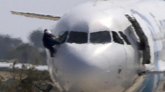 Un miembro de la tripulación abandona el avión secuestrado. YIANNIS KOURTOGLOUREUTERS