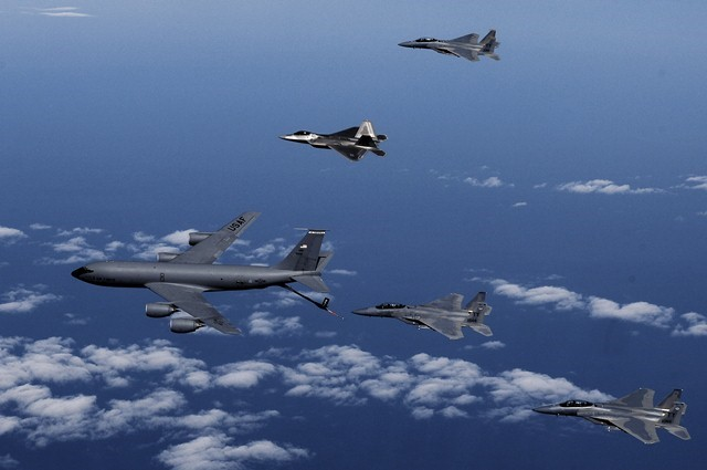 F-15 y F-22 en observación derecha esperando para repostar en vuelo, F-15 en pre-contact listo para repostar y otro en reagrupamiento izquierda una vez repostado y a la espera de reunir la formación.
