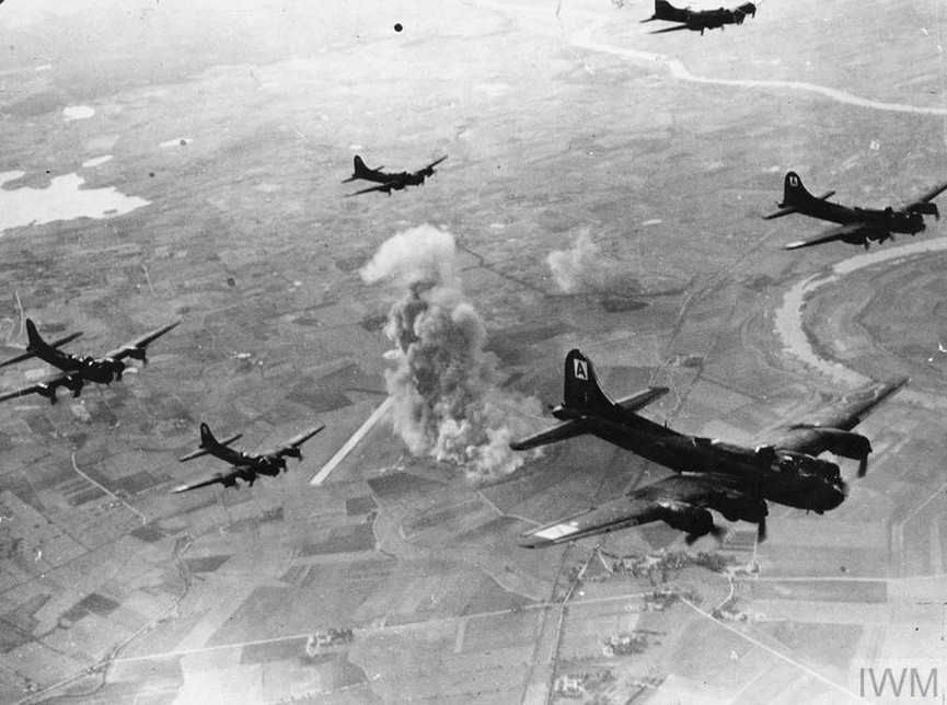 Formación de Boeing B 17 Flying Fortress en acción sobre Danzig. Estos bombarderos, junto con los Consolidated B 24 Liberator dotaban a la Octava y a la Decimoquinta Fuerza Aérea, y realizaban de día el trabajo que el Bomber Command continuaba de noche. A pesar de su potente armamento defensivo que llegaba hasta la docena de ametralladoras pesadas de 12,7 mm, las pérdidas alcanzaron tal escala que tuvieron que suspender las operaciones tras las carnicerías sucesivas de Regensburg y Schweinfurt. No pudieron volver al corazón del Reich hasta disponer de la escolta de los cazas de largo alcance P 51 Mustang, cuando éstos por fin dispusieron de los motores británicos Merlin y pudieron prescindir de los Allison.