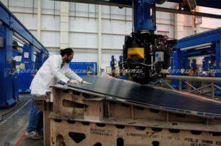 Un técnico de fabricación inspecciona un panel compuesto de fibra de carbono del timon de cola de un B777 en una máquina automática de colocación de cinta en las instalaciones de fabricación de materiales compuestos de Boeing en Frederickson, Washington.