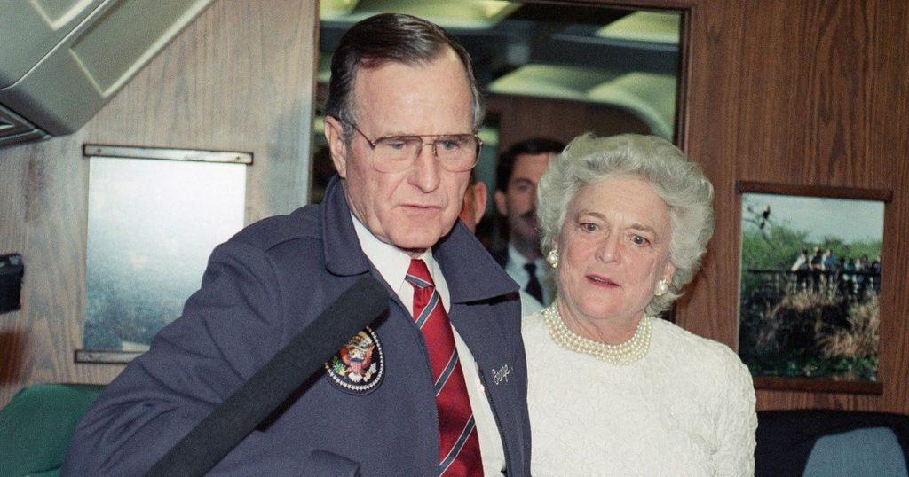 El presidente George H.W. Bush habla con los reporteros del Air Force One mientras la primera dama Barbara Bush observa el 9 de febrero de 1990. (Robert Daugherty/AP)